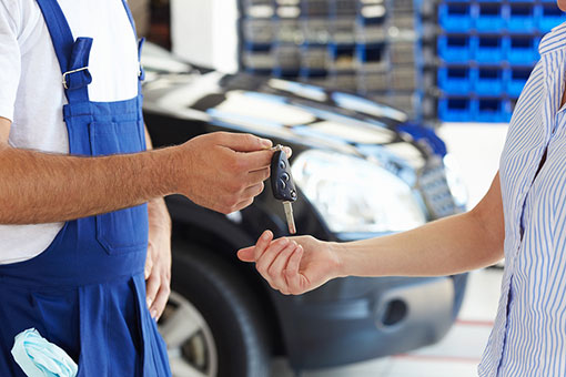 Mechanic handing keys to driver after collision repair services